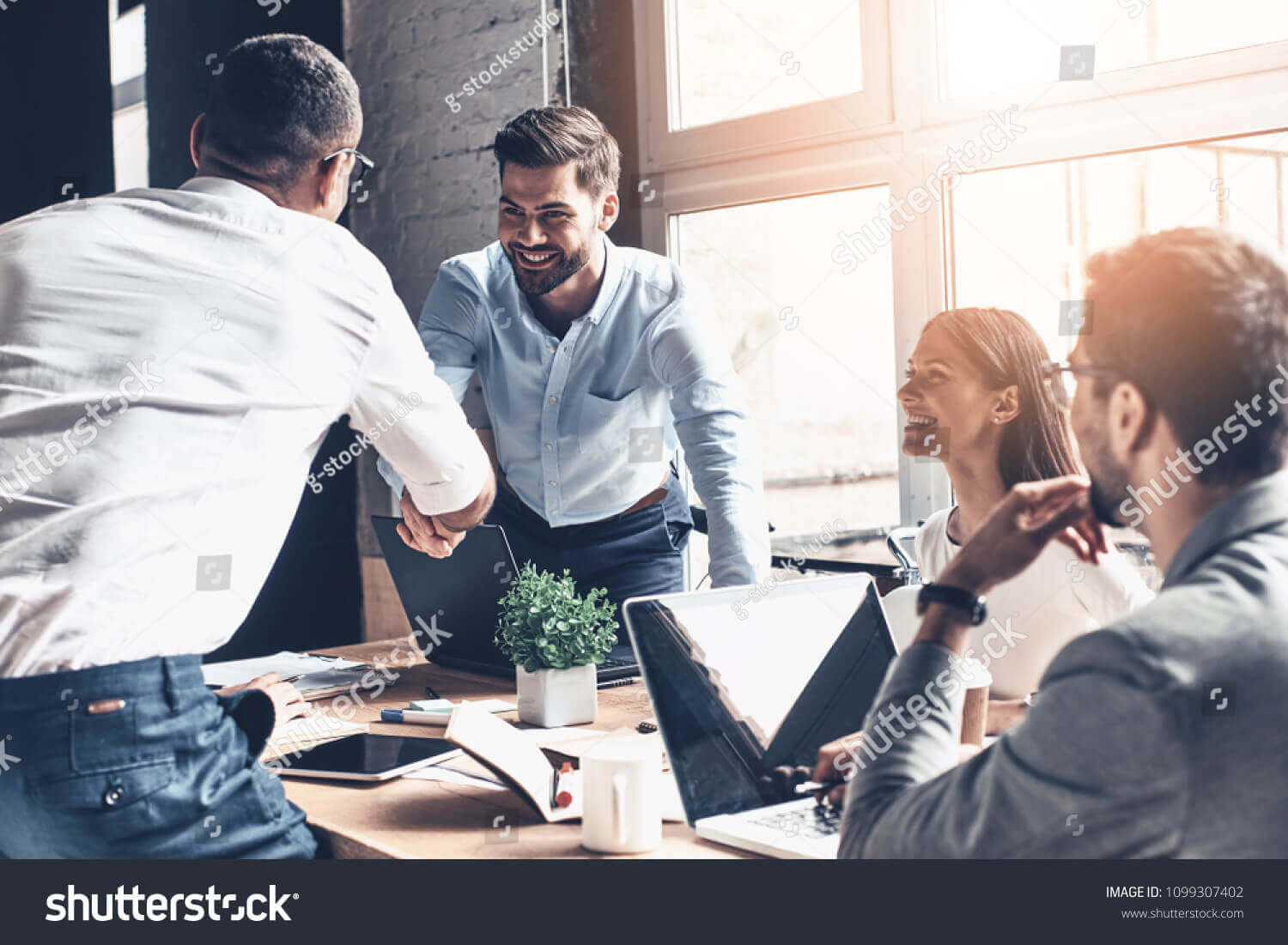 stock-photo-glad-to-work-with-you-young-modern-men-in-smart-casual-wear-shaking-hands-and-smiling-while-1099307402