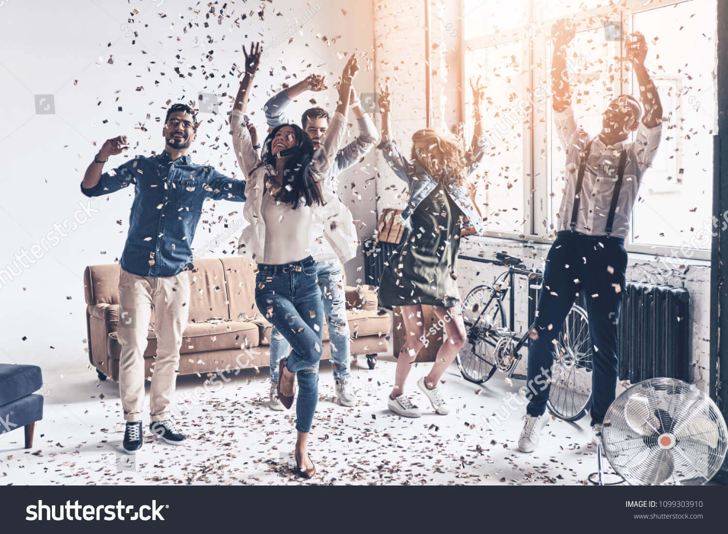 stock-photo-so-much-fun-full-length-of-happy-young-people-dancing-while-spending-time-at-home-with-confetti-1099303910