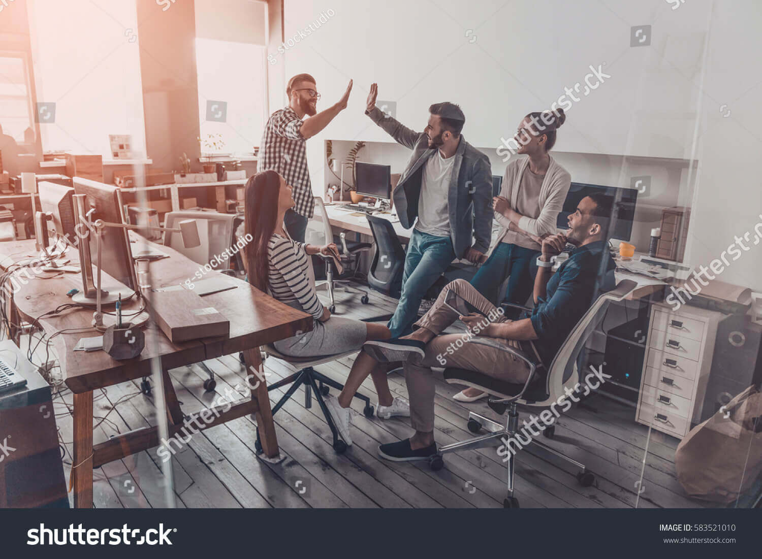 stock-photo-we-did-it-two-cheerful-young-business-people-giving-high-five-while-their-colleagues-looking-at-583521010
